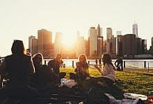 Young people having a picnic in a park in New York City at sunset